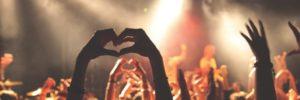 hand making heart shape in a crowd